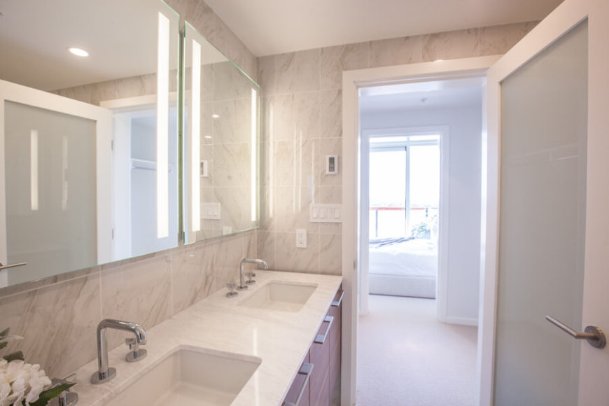 Here we see the subtle embedded lighting within the mirrors, as well as the view across the hall toward one of the bedrooms, awash in natural light.