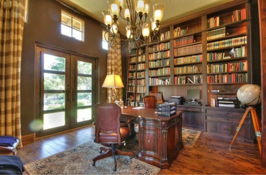 this opulent home library doubles as a large home office with rich wood bookshelves filling built home library