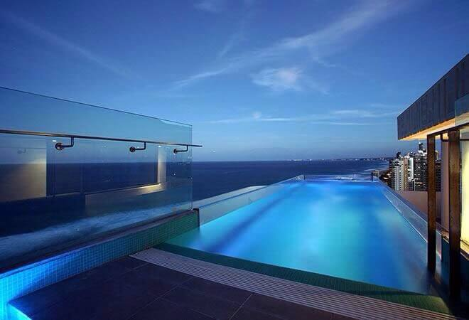 This glass-sided pool creates an stunning visual as it looks out over the ocean. The lighting, when combined with the glass gives the water an interesting cloudy look.
