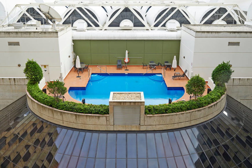 This quiet space makes for a lovely private pool and patio area. Surrounded by shrubs and small trees above a glass dome, this uniquely shaped pool is beautiful.