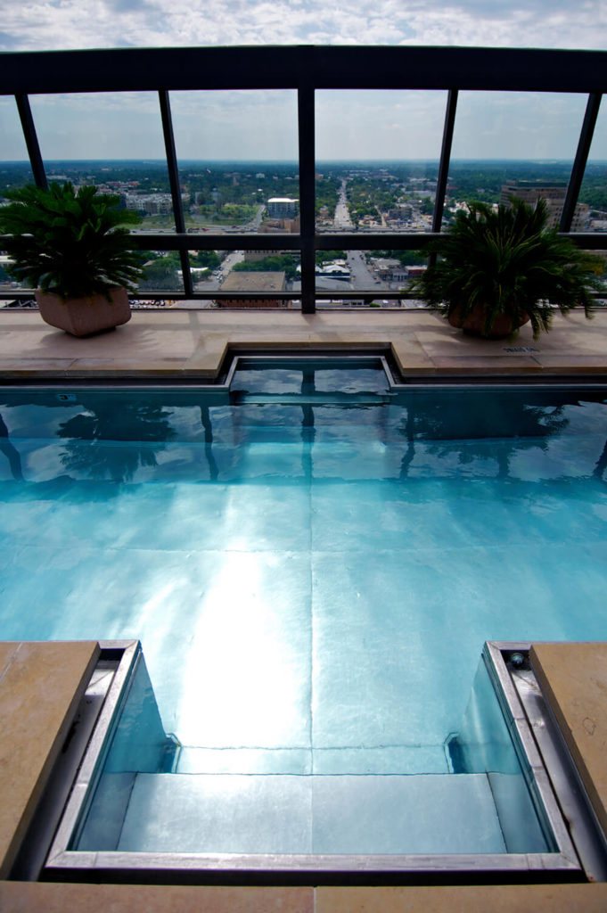 This gorgeous, metallic bottomed pool creates a unique and interesting look to the pool itself. The floating tile around the pool balances the silver of the metal pool with a more natural look.