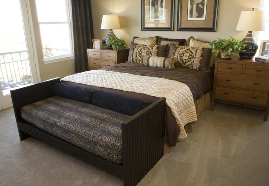 Decorative pillows again create a faux headboard and add to the room with  bold patterns to