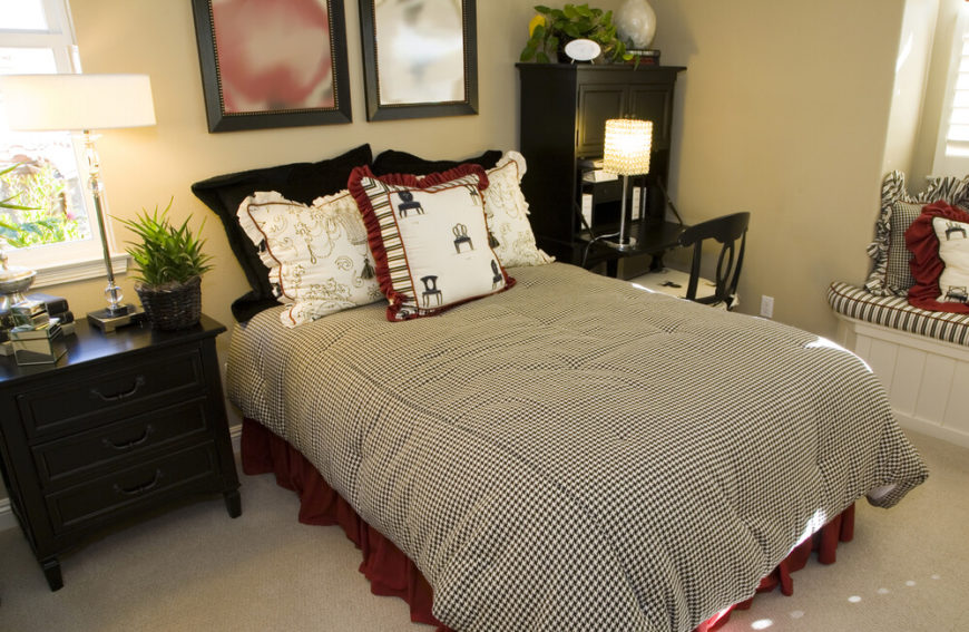 the black white and red color scheme of this bedroom against the plain beige