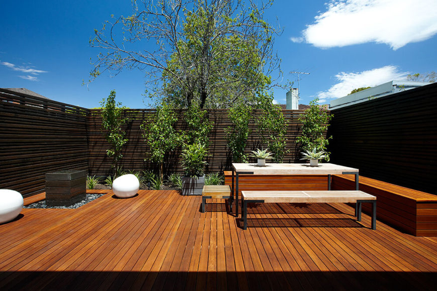 Here we take a second look at the patio, this time during the bright light of day. The carefully chosen foliage and slim plank fence ensure privacy and comfort in this exquisitely crafted outdoor space.