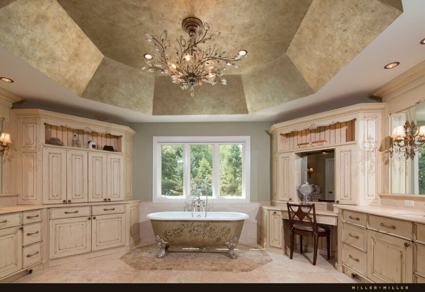 This massive bathroom space is amplified by a high vaulted ceiling, and accented by a large crystal chandelier. The clawfoot tub sits centered beneath a window, and features detailed patterns on the outer surface. A large vanity is featured between the tub and the counter.