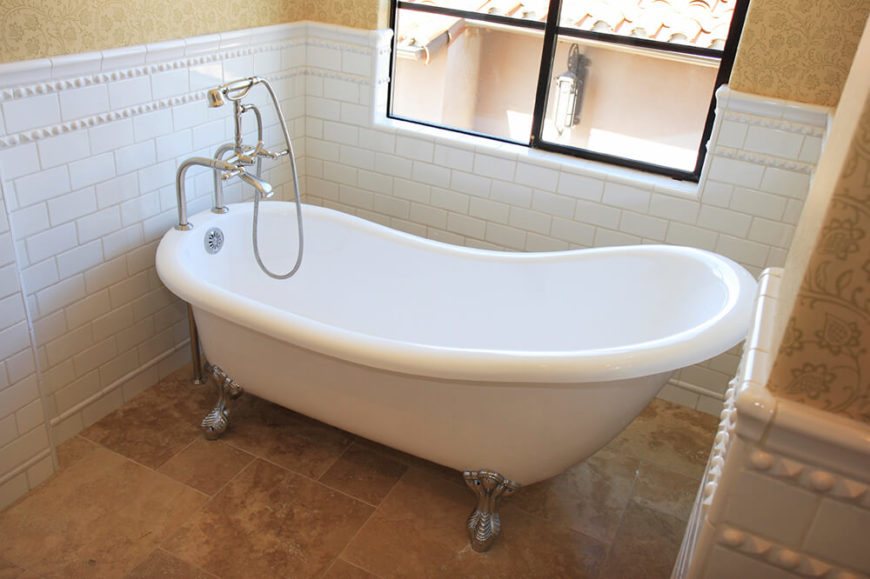 This clawfoot tub sits upon textured tile and directly beneath a window  space is 27 Relaxing Bathrooms Featuring Elegant Clawfoot Tubs PICTURES