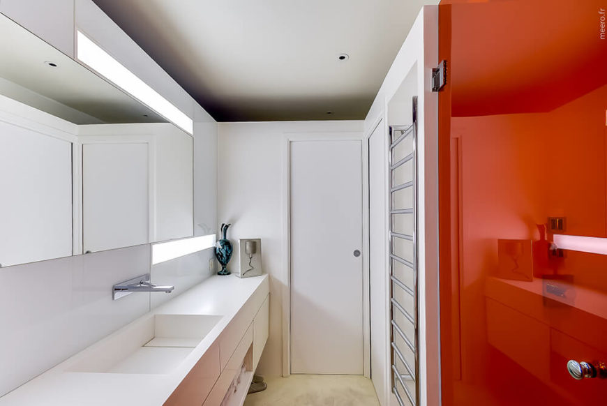 The bathroom is mostly white, yet bursting with color courtesy of the red glass shower door at right. A stainless steel drying rack is built into the wall, across from a sleek white vanity with wall mounted plumbing.