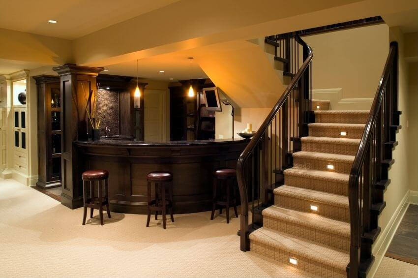 basement home bar with a curved bar and an opening to the family