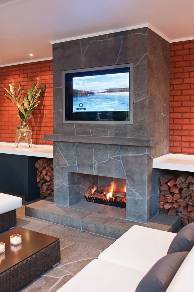 The large fireplace here is wrapped in marble and flanked by a pair of wood storage voids, with a television mounted behind glass above. This space is designed to be as comfortable as a living room while enjoying the outdoors.