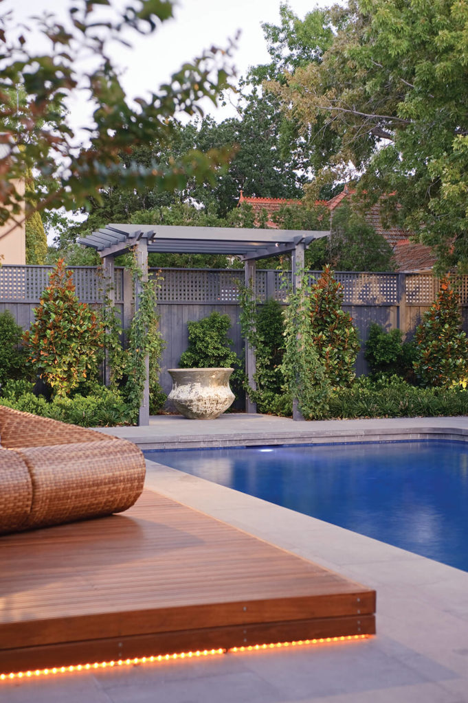 Now we look across the pool and the secondary natural wood deck, which we can see is lined with more subtle lighting. The large urn is surrounded by lush greenery and the dark hued fence is virtually obscured by nature.