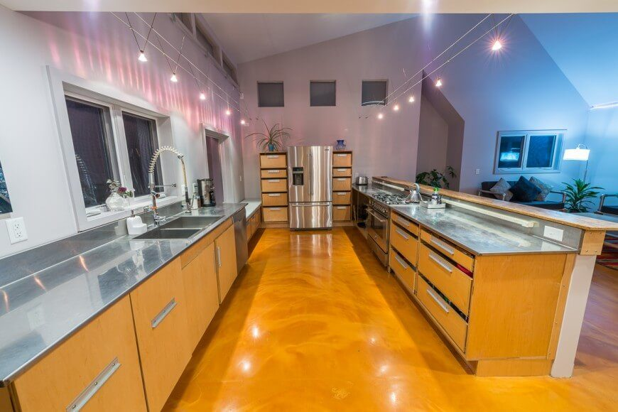 An industrial style kitchen with rail lighting, stainless steel countertops, and plenty of lower storage, while wall cabinets are absent. The kitchen looks out over the small living room and entry. The glossy floors are utterly unique.