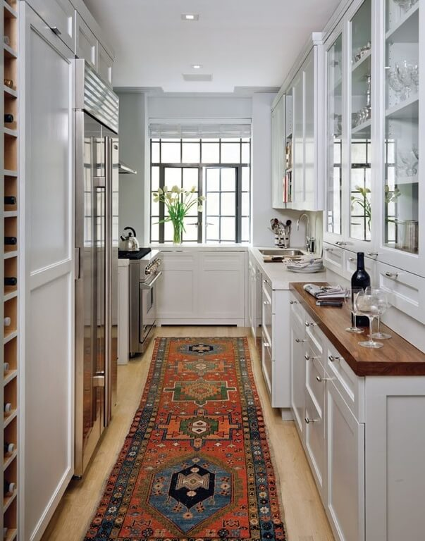 A Slim Galley Kitchen With A Built In Wine Rack And Pantry Next To The