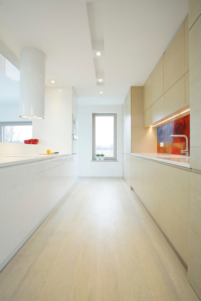 This minimalist kitchen looks almost featureless, but a bold multi-colored backsplash provides a focal point for the galley design.