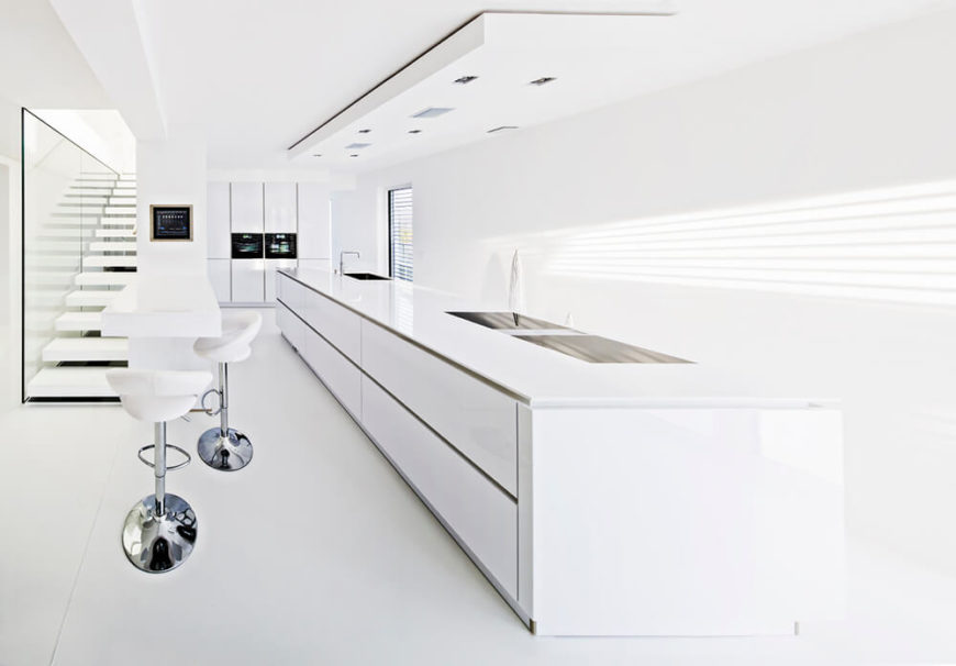 This 3-D rendered modern and minimalist white kitchen isn't one you're likely to see outside of a show room, since the slightest attempt at cooking could leave a serious mess, but the design itself features a massive functional island, a secondary eat-in bar near the stairwell, and multiple windows.