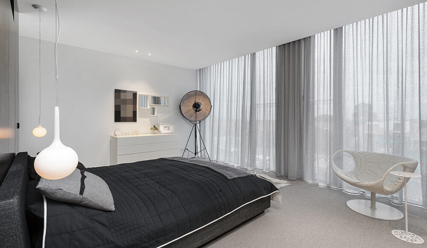 The master bedroom, on the upper floor, features more of the full height glazing on the back of the home, offering unparalleled outdoor views. The neutral color palette is contrasted with black bedding and accent wall.