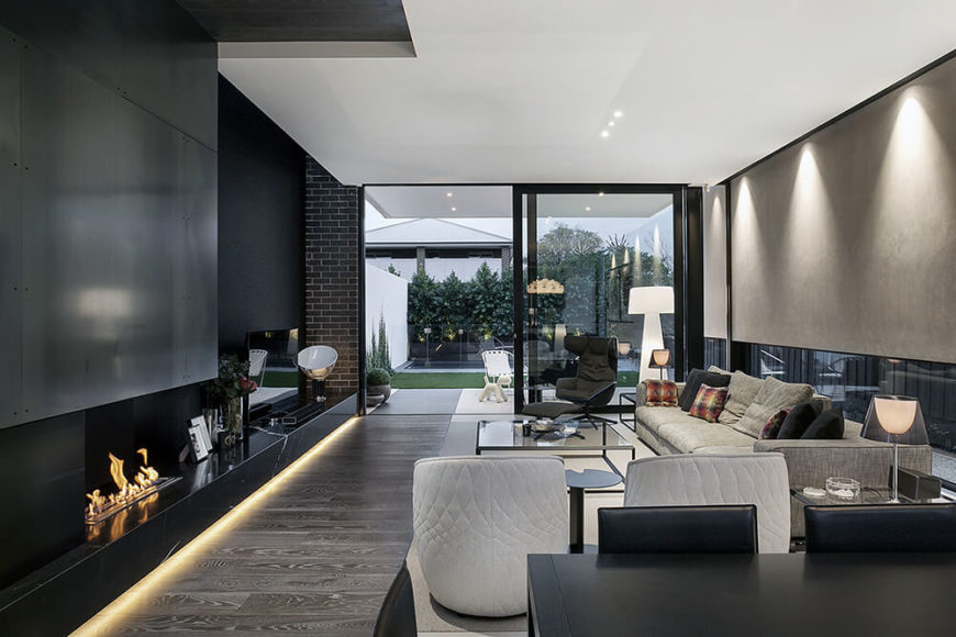 In the center of the massive open space at the heart of the home, we peer over the dining table into the living room space, flush with contemporary furniture in neutral tones. From here we can see directly across the backyard landscape through full-height glass panels.