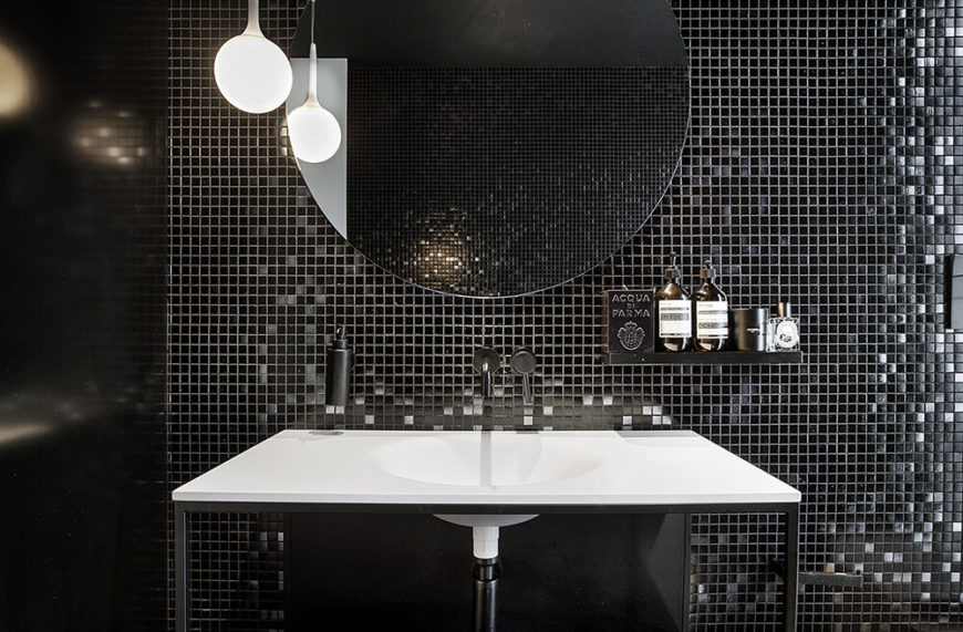 The bathroom is highlighted by a deep attention to texture, with a micro-tile wall backing an open design vanity with broad countertop sink. A single circular mirror hangs above the wall-mounted faucet.