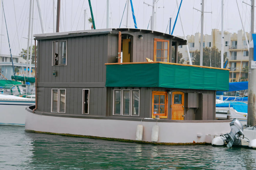 Another permanently moored houseboat located in a large coastal marina. The home is two stories, with plenty of windows and a balcony.