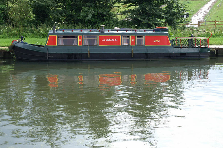 A large mobile houseboat in the Netherlands in a deep forest green with bold red and yellow panels.