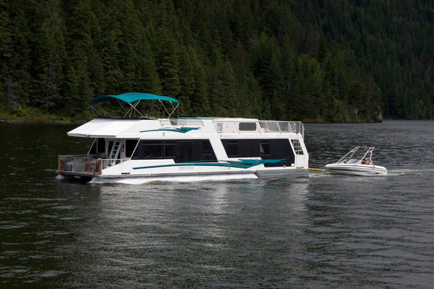 A sleek houseboat with a large upper deck and large tinted windows to preserve privacy while still allowing the owners to view the landscape.