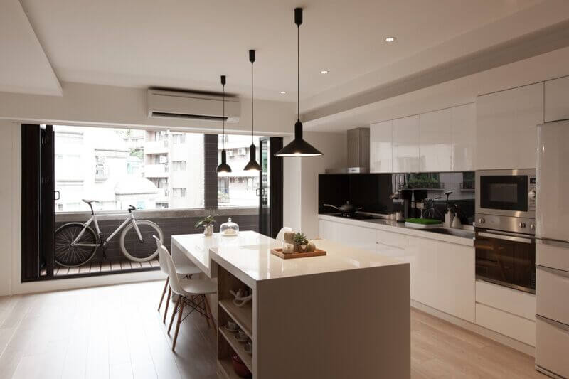 Simple white chairs fit the sleek modern design of this kitchen. High-gloss  white
