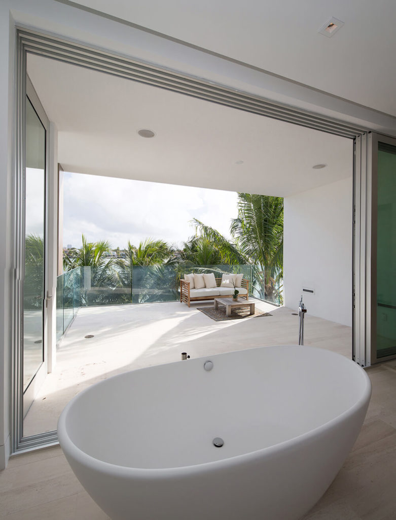 From inside the master bathroom we can see the outdoor terrace, which is surrounded by glass balustrades and shaded from view by a series of tall palms that surround the back of the propert