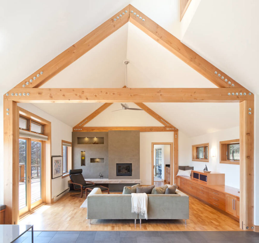 Moving inside the home, we can see how rich natural wood informs the entire design. Natural wood beams cross an expanse of white vaulted ceiling in the living room.