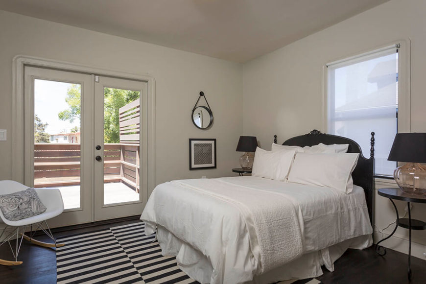 The master bedroom also features a set of glass French doors for easy and direct access to the deck and the outdoors. The simple white room is enlivened with a corner accent chair in the same white and natural wood style as the dining set.