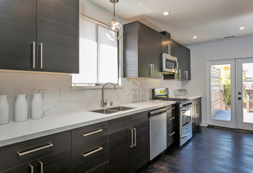 The completely refreshed kitchen is awash in dark wood cabinetry, matching the tone of the hardwood flooring throughout the home. Stainless steel appliances and a white marble backsplash add a dose of luxury.