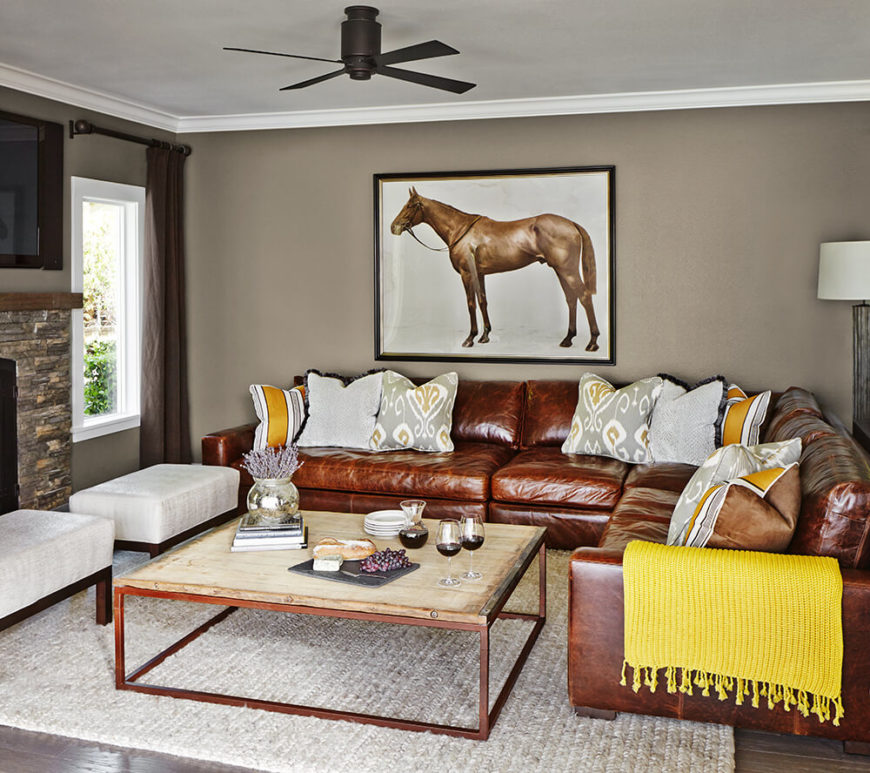 The living room is defined by a large plush leather sectional, wrapping a space that includes a pair of thick cushioned bench ottomans and a massive industrial coffee table with natural wood top. A stone wrapped fireplace at left anchors the room.