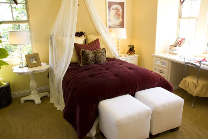 A canopy is lightly draped over the head of this twin bed, with white footstools at the end of the bed and white bedside tables. The deep maroon comforter contrasts the rest of the light colors in the room, and the desk space is illuminated by natural light spilling in from the window.