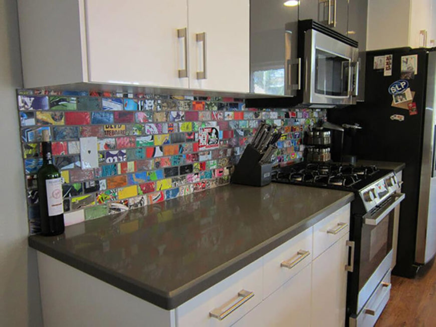 With a similar look to the kitchen featured above, this private customer has a board art backsplash behind their stove and working countertop area. The reflective countertop compliments the backsplash art, and the variation between dark colors, light colors, and the board art makes this kitchen space unique and aesthetically appealing.