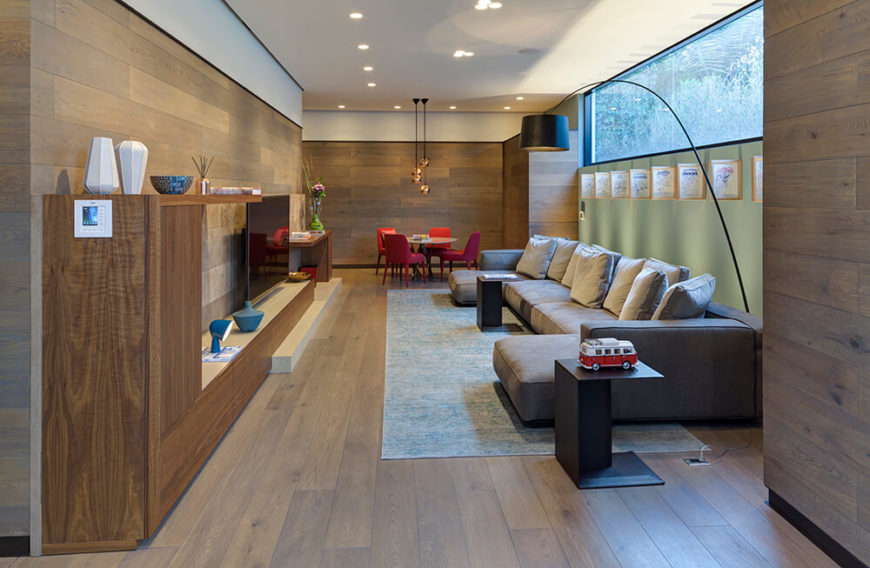 This private upper-level family room space is made warm by the abundance of rich natural wood and smaller windows than seen on the other side of the building. A massive sectional defines the space, facing a neatly integrated entertainment shelf.