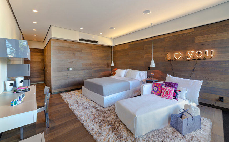 """This guest bedroom is entirely wrapped in the warm wood paneling seen elsewhere, spiked with white furniture and colorful accents. A series of floating storage shelves and desk stand across from a wall mounted with a neon """"I <3 you"""" sign."""