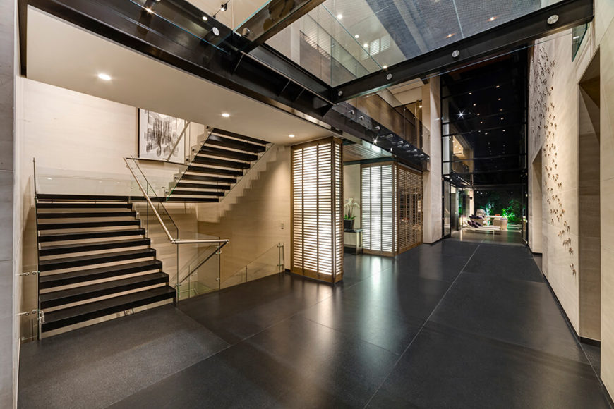 At the center of the home, bridging the two volumes, is the double height lobby space. Here we see an open structure wrapped in limestone, steel, and glass, accented with expertly placed natural wood elements.