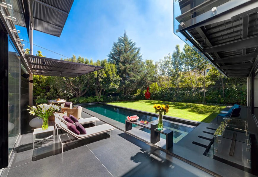 A good portion of the wraparound patio is sheltered either via large shades extending from the structure, or from the second floor balcony, providing a comfortable outdoor relaxation space.
