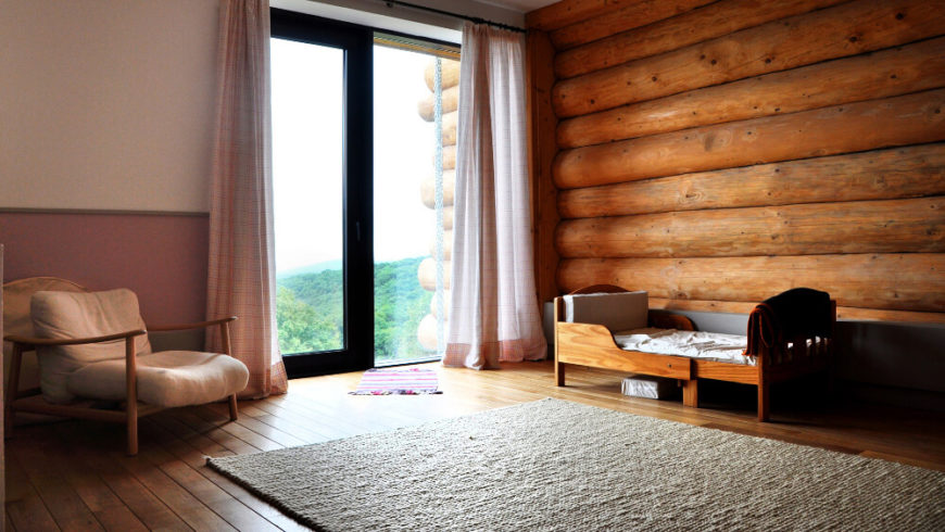 This cozy room is set up as a nursery for a small child, with a natural wood bed and large loosely cushioned armchair the only visible furniture. The sliding glass door here provides direct outdoor access.