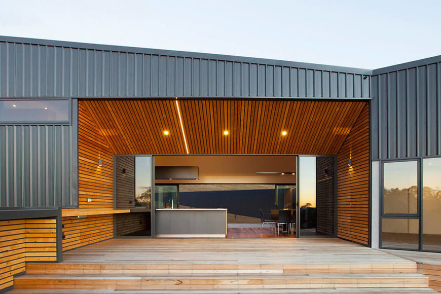 This large entrance to the home creates a welcoming atmosphere, opening directly into the kitchen and dining area. The profiled metal cladding exterior contrasts the rich wood paneling leading into the interior. Since the actual entrance to the home recedes so far into the structure, a sheltered outdoor patio is created.