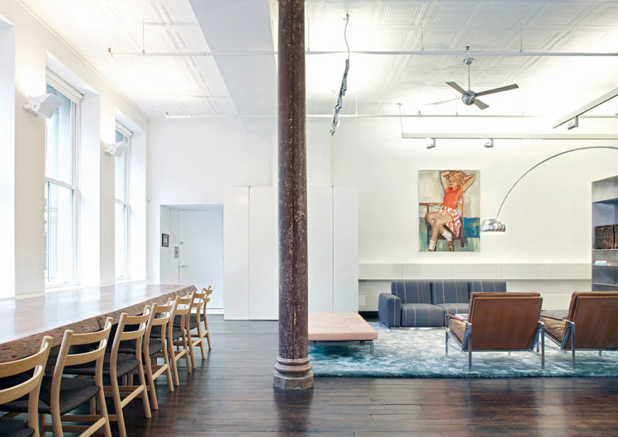 The front door can be seen in the left corner opening into the living space. Bold wall art and stainless steel accents throughout the room offsets the white walls and ceiling. The furniture was chosen for both comfort and looks and it perfectly compliments the contemporary design of the loft.