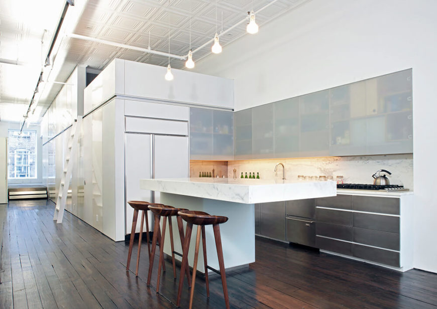 The kitchen fits snuggly in the corner of the living space. The lower cabinets are made up of stainless steel to carry the accent through from the rest of the space. The upper cabinets are made from solid pieces of acrylic to create light blocks to help brighten up the kitchen when it is needed.