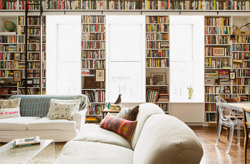 The huge living and dining room space is utterly dominated by bookshelves from floor to ceiling, framing large windows with built-in seats for enjoying the surrounding views.