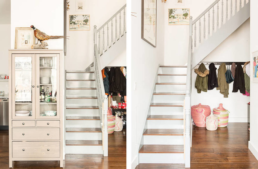 At the bottom of the staircase, we see both an ornate, traditionally styled display case at left, with the kitchen in the background, and the under-stairs coat storage, at right.
