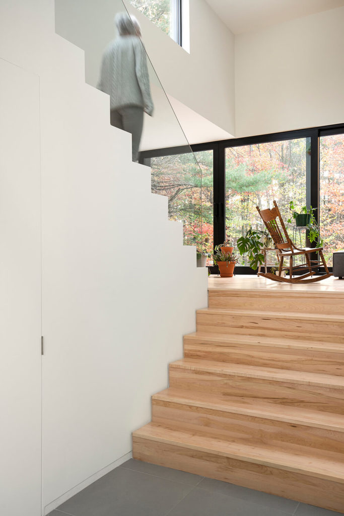 As we enter the home and start up the stairs, we are greeted by light wood grain steps and a wonderful view outside the window across the house. The high ceiling helps to really open up the space and welcome anyone who enters.