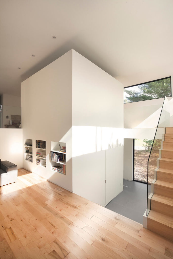"This angle reveals the large ""block"" which is the central unit which this house was designed around. The staircase wraps up and around it, and into the private bedroom suite. However, it does not extend to the ceiling and there is an opening to the bedroom on the other side, giving this home its open atmosphere."