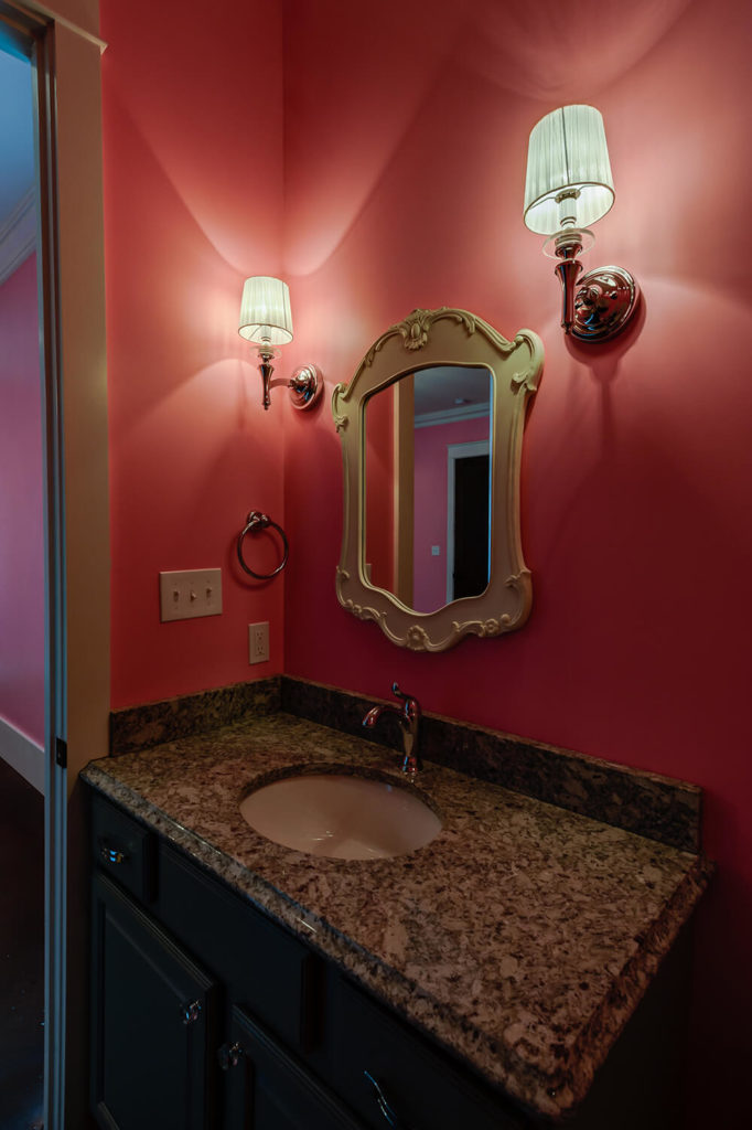 The bathroom features the same bright pink walls as the bedroom it is attached to. Contemporary wall sconces highlight the silver fixtures in the room and flank the gorgeous mirror. A speckled granite countertop lightens up the dark cabinets.