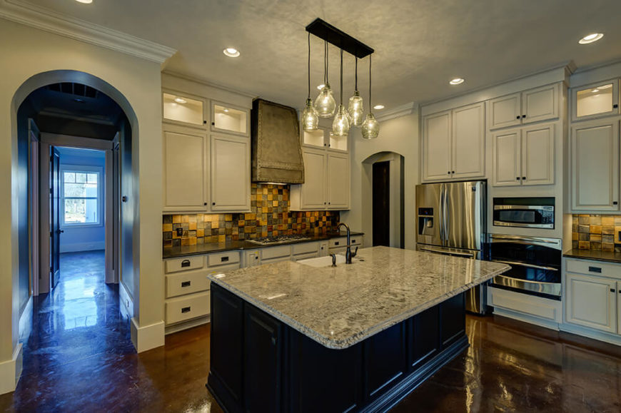 The kitchen features the same floors and bright white cabinetry to keep the space in the heart of the house feeling bright and open. Contrasting granite countertops add to the room and the rustic feel is continued in the stove hood, rough tile backsplash, and repurposed glass bottles in the light fixture.