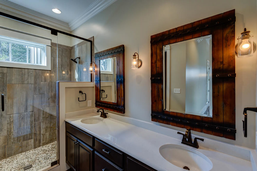 The master bathroom features bright white counter tops, dark cabinets, and more reclaimed barn wood. Rustic touches and industrial style lights carry the decor through the room and complements the natural stone in the shower.