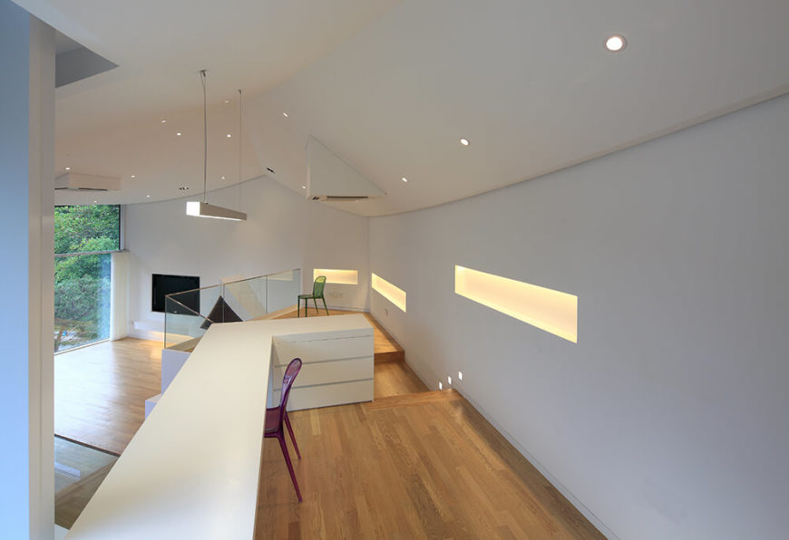Pulling further back, we can see sets of lit shelving coves built into the walls, as well as a bevy of subtle recessed lights spanning the vaulted ceiling. The rich wood flooring here acts as a natural anchor for the bold white space.