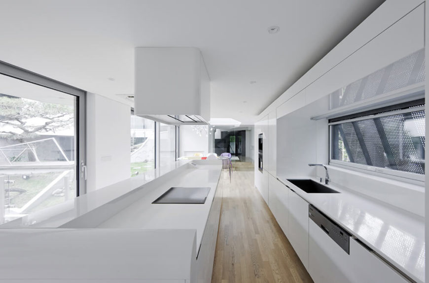 The lengthy galley kitchen stretches between sets of large windows to the left, overlooking the courtyard, and smaller windows to the right, shaded by louvers for utmost privacy.