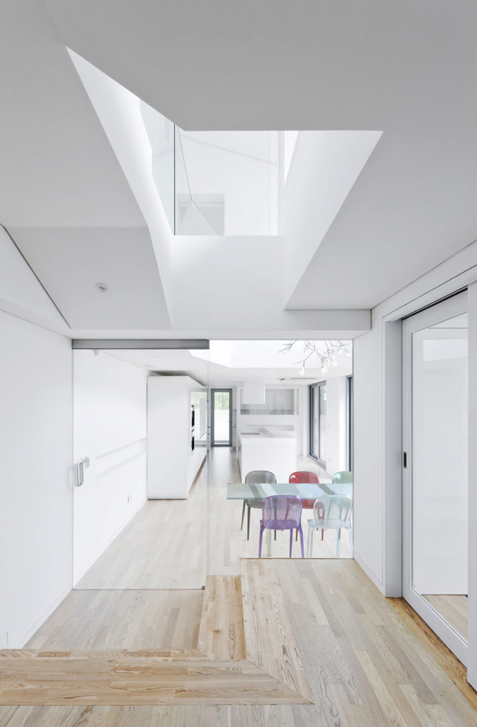 Through seamless interior glass doors, we see the kitchen and dining area, with multicolored chairs spiking the predominant white and natural wood color palette.